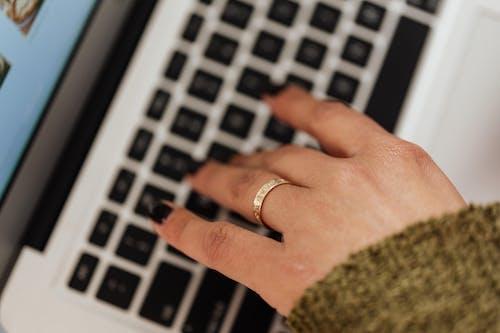Crop woman typing on modern laptop keyboard