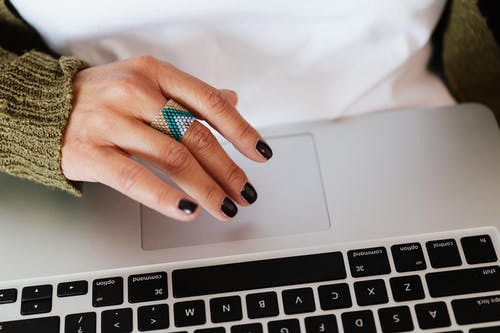 Crop woman with stylish ring using laptop
