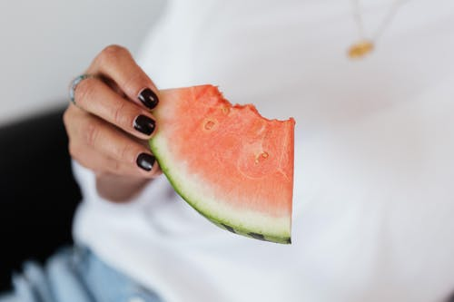 Crop unrecognizable female with manicure in white t shirt eating sweet juicy watermelon