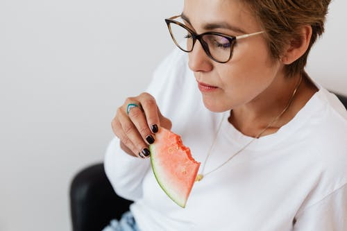 Crop adult lady eating tasty watermelon at home