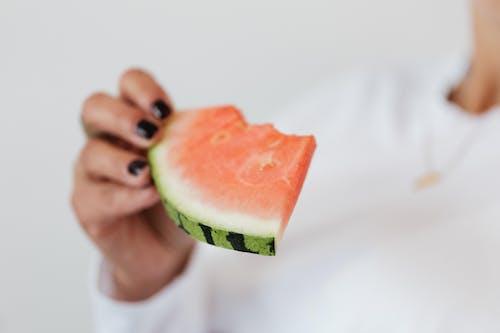 Bitten slice of fresh sweet juicy watermelon in hand of crop faceless female in white sweater