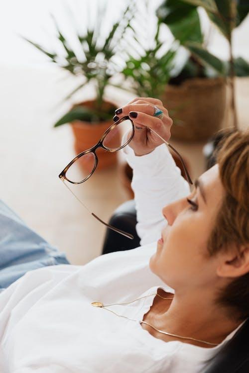 Crop upset female sitting in armchair with eyeglasses in hand
