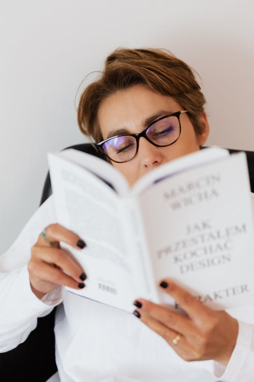 Adult female in casual clothes and eyeglasses holding book with white paperback in hands and reading