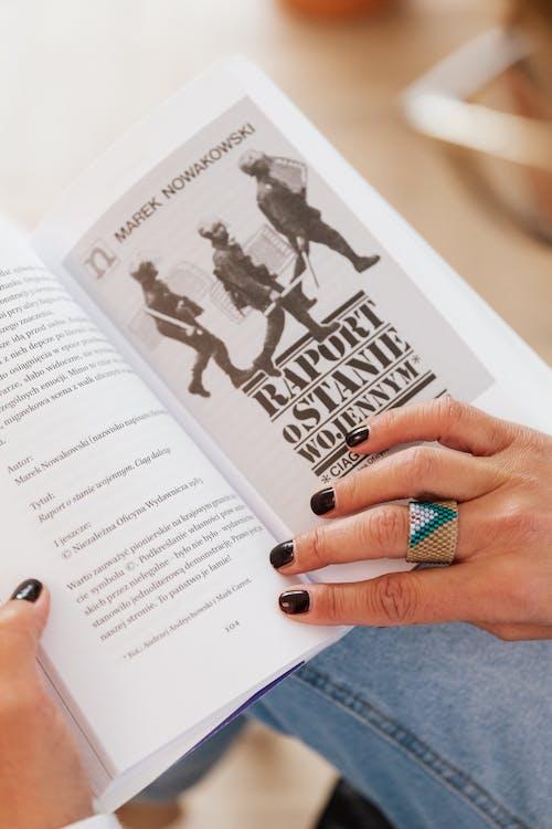 Faceless woman paging graphic novel at home