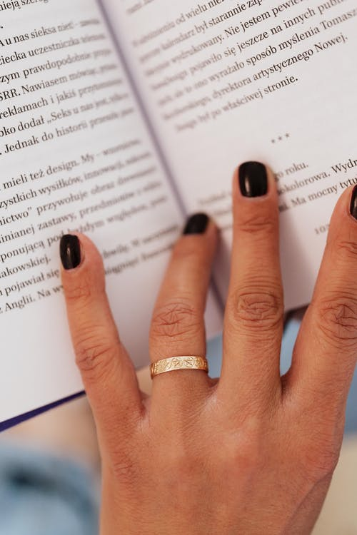 Anonymous woman holding hand on book while reading
