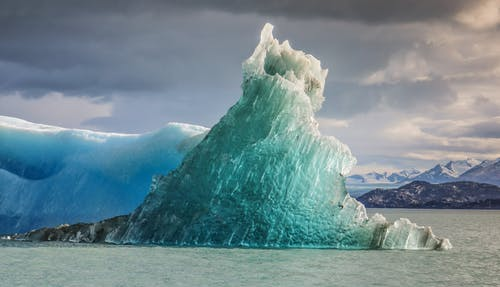 Huge blue iceberg located in cold sea water against dark stormy sky with gray clouds
