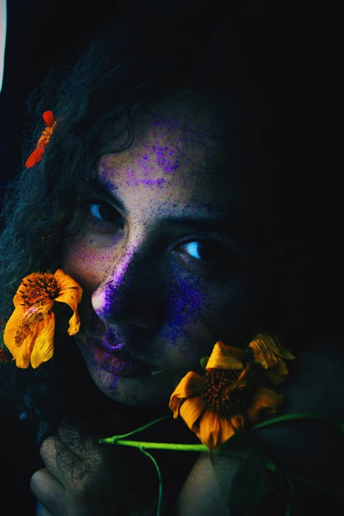 Woman With Purple and Yellow Flower on Her Face