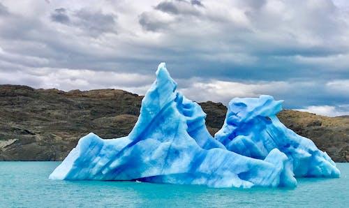 Icebergs in sea near rocky shore