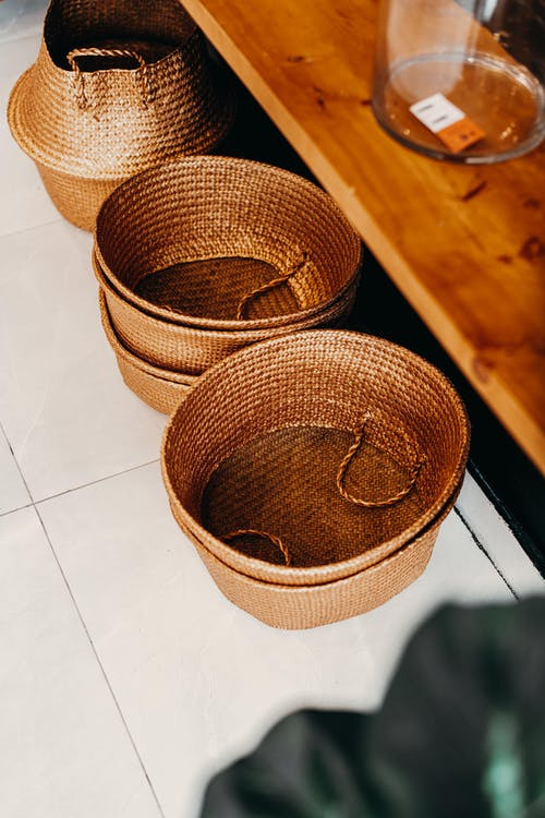 Wicker baskets on floor near shelf