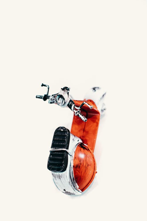 From above toy vintage motor scooter with chrome handlebar placed on gray background