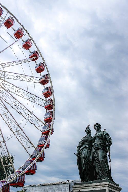 Ferris wheel near bronze monument against cloudy sky