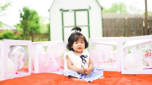 Full body of cute kid in dress sitting on blanket with baby letters during party in yard