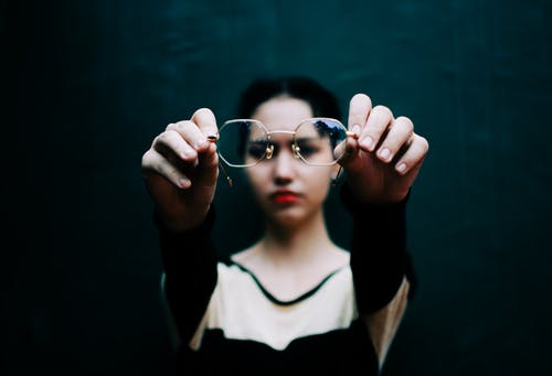 Young woman showing stylish eyewear against black wall