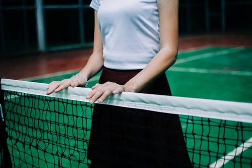 Person in White Shirt and Black Shorts Standing on Green and White Net