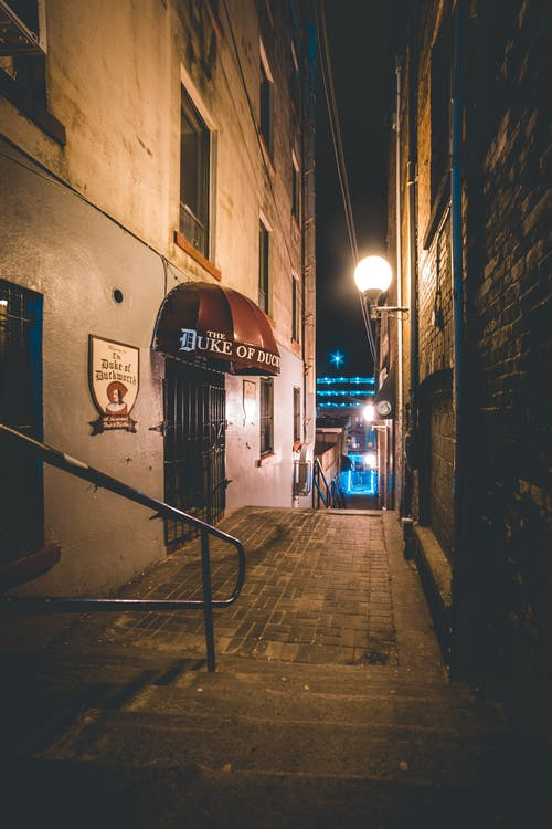 Narrow staircase in alley at night