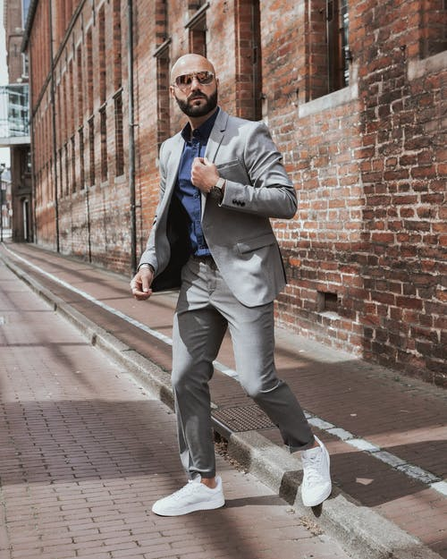 Full body of serious male in stylish formal wear and sunglasses walking on pavement against brick building