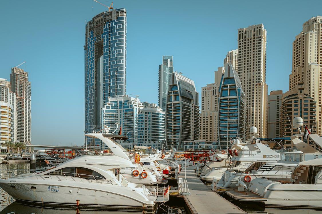 城市建築附近的碼頭上的白色遊艇