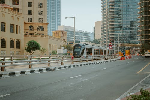 Modern metro train moving along high towers and road in central district of city