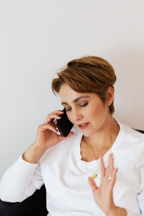 Stylish lady conversing on smartphone and showing stop gesture