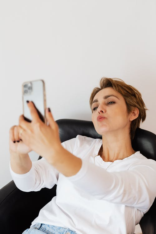 Woman taking selfie on smartphone pouting lips