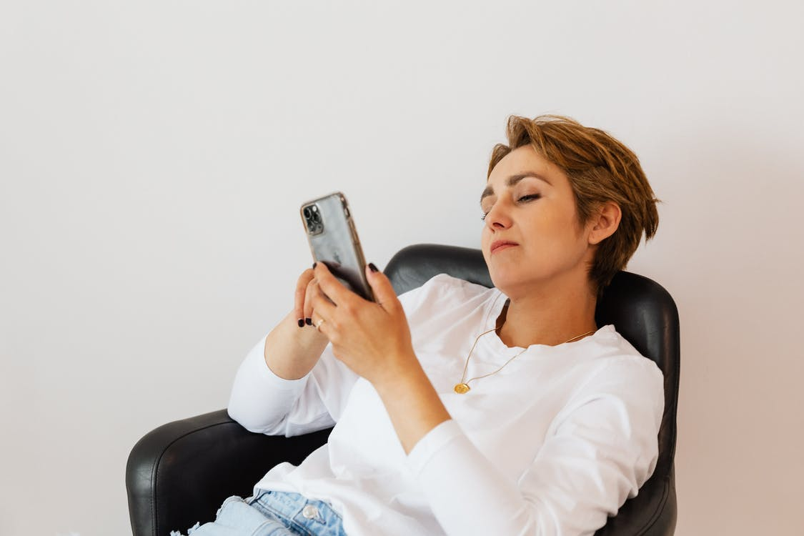 Calm woman surfing internet on smartphone while sitting on chair