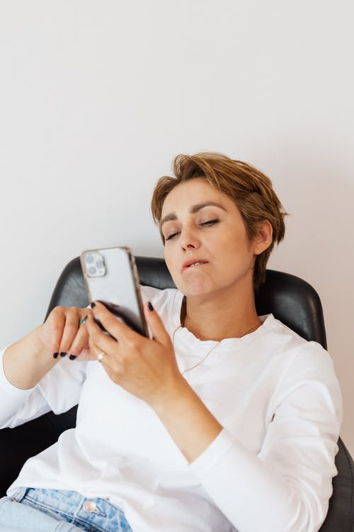 Adult thoughtful lady in jeans and white blouse with manicure using social media on cellphone while sitting on cozy leather chair on white background