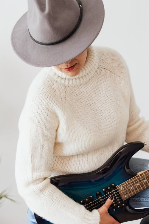 Female musician in white knitted sweater and stylish hat performing on modern electric dark blue guitar against white wall