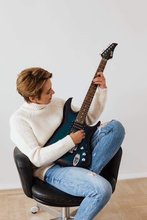 Focused female musician wearing jeans and white knitted sweater sitting on black leather chair and performing electric dark blue guitar against white wall