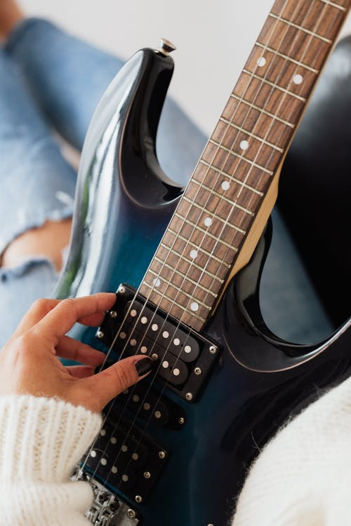 From above of crop anonymous female musician in warm sweater and jeans playing electric guitar while resting in comfortable armchair