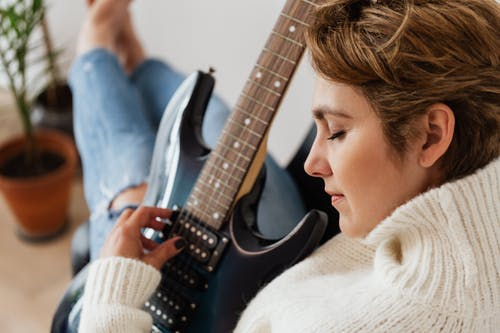 Crop woman playing electric guitar with pleasure
