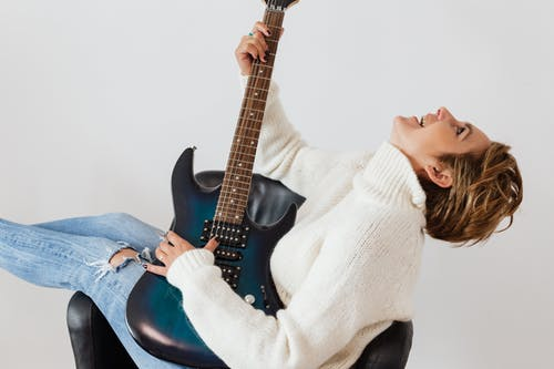 Joyful woman having fun while practicing guitar