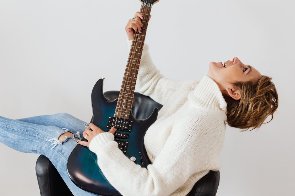 Joyful woman having fun while practicing guitar
