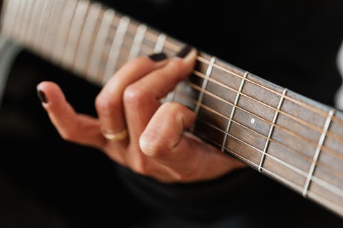 Crop unrecognizable female guitarist practicing chords on musical instrument during rehearsal in studio