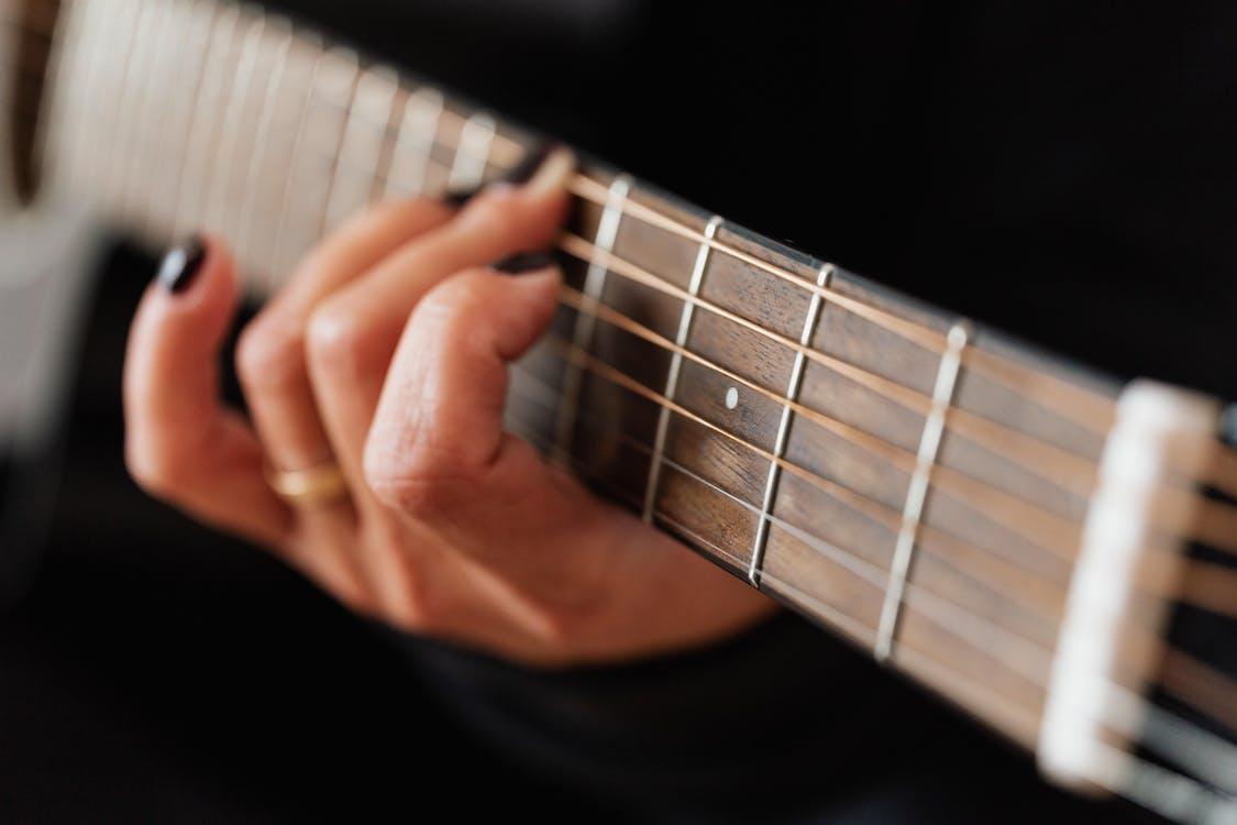 Crop faceless woman practicing classical guitar technique