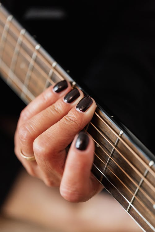 High angle of crop anonymous female musician with dark manicure performing song on electric guitar during music lesson