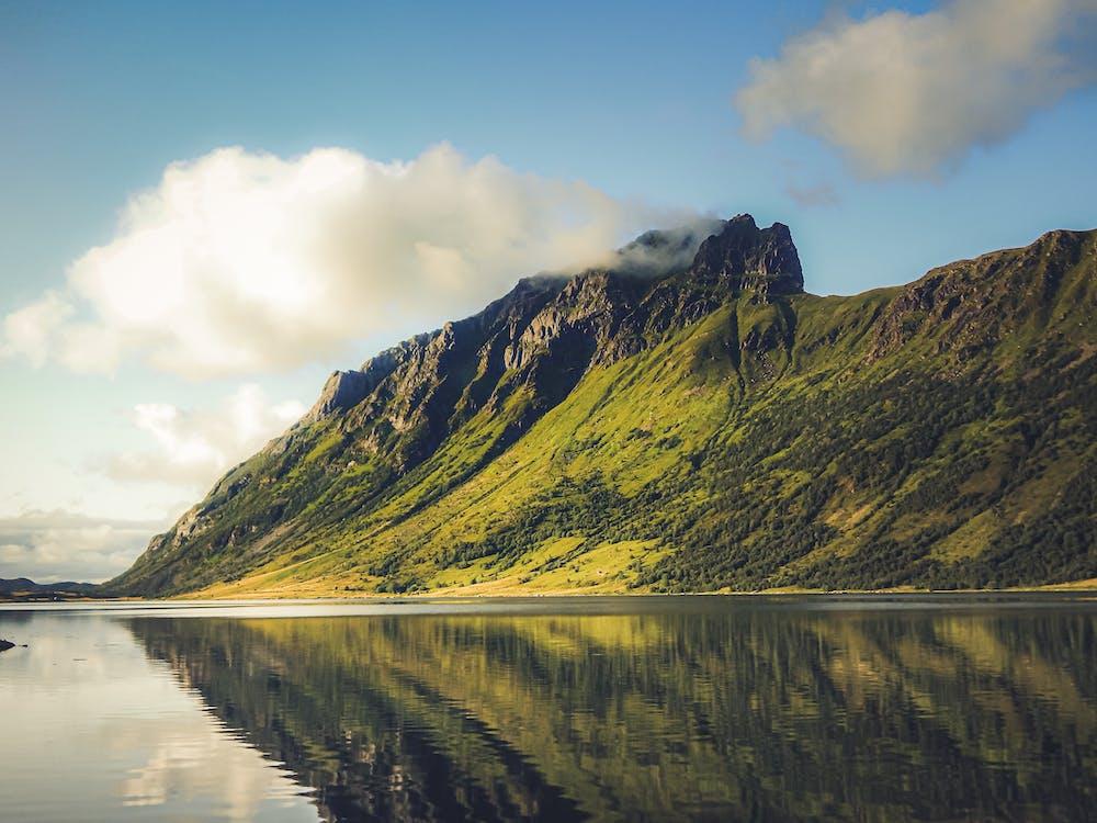 Green Mountain Beside Lake Under Blue Sky
