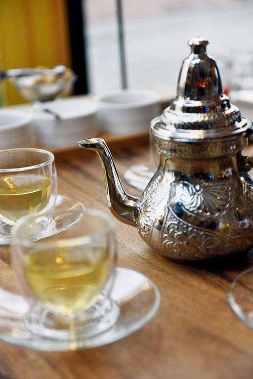 A Stainless Steel Teapot Beside a Cup of Tea