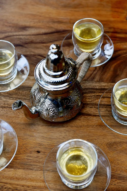 A Stainless Steel Teapot Beside a Cups of Tea on a Wooden Surface