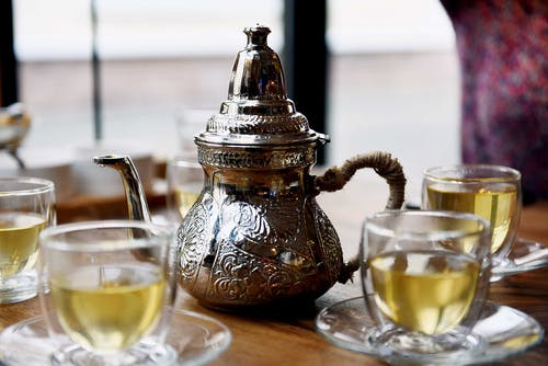 A Stainless Steel Teapot Beside a Cups of Tea