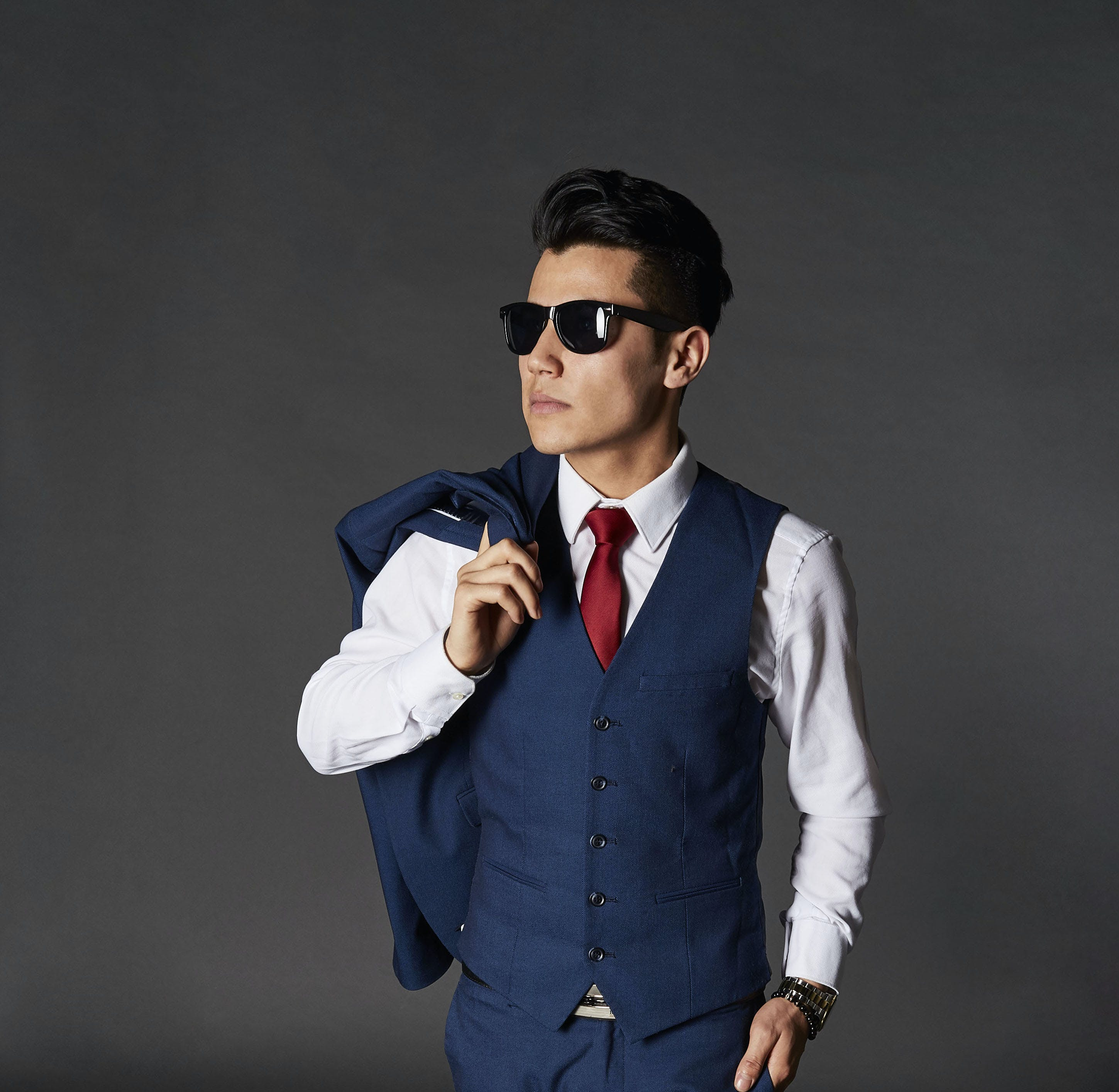 Man Wearing Blue Suit Posing Against Gray Wall