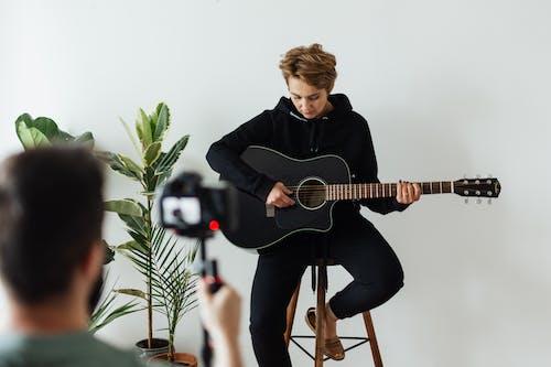 Foto stok gratis alat musik, bangku kayu, bermain gitar, celana hitam
