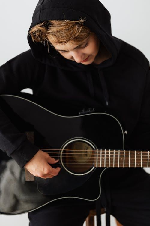 Darmowe zdjęcie z galerii z czarna bluza z kapturem, czas wolny, gitara akustyczna, grać na gitarze