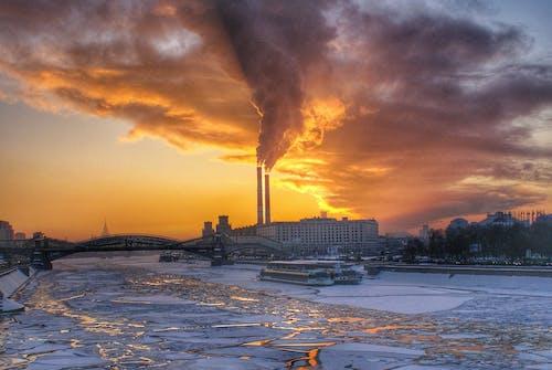 Smoke from plant chimneys under bright sundown sky