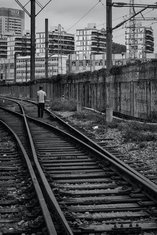 Man walking on tracks of railway