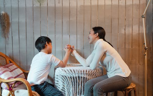 Happy smiling mother and son wearing casual clothes sitting on wooden chairs and competing in arm wrestling in rural house