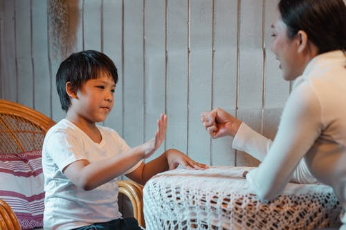 Happy smiling Asian mother and cute boy wearing casual white shirts playing rock paper scissors game against gray plank wall