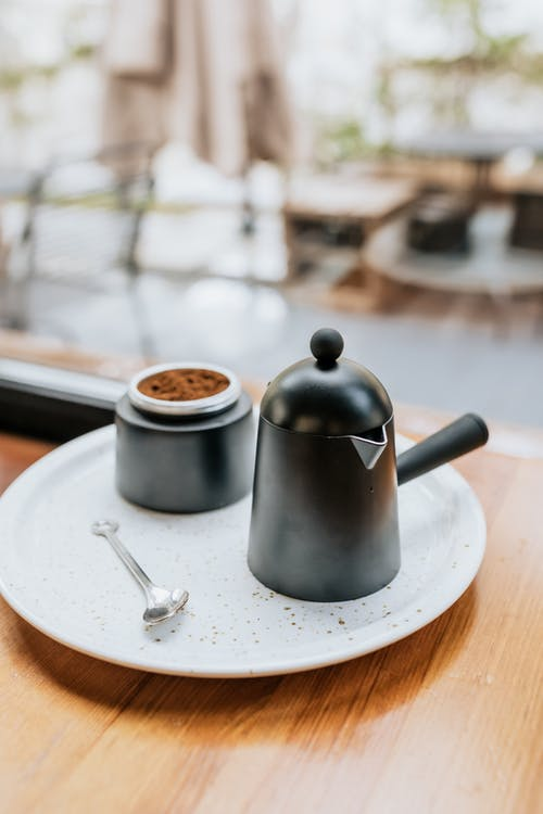 Stainless Steel Teapot on White Ceramic Plate