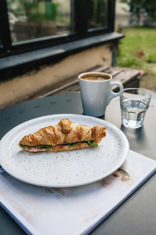 A Bread on a Plate beside a Mug and Glass