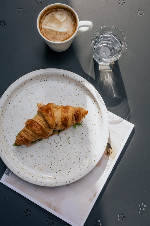 Top View of a Bread on a Plate beside a Mug and Glass
