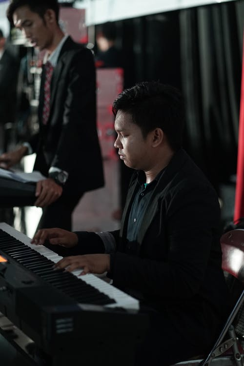 Man in Black Coat Playing Piano